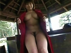 An Asian girl who is naked underneath her long coat is talking to the cameraman, obviously sufferi