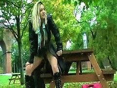Hot blond fucks herself with a huge dildo in a public park