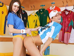 Two teenage girls are playing with some footballs in the dressing room. Soon they they strip off part of th