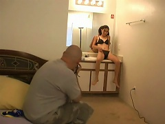 Go behind the scenes and watch as this bald man shoots some pictures of this stunning brunette chick whos sitting on this ta
