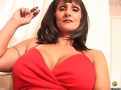 Stunning in her lovely red dress, Horny vixen Corina smokes enticingly in her hand while fondling  her pierce