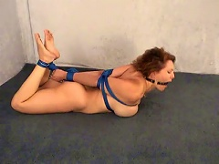 See this helpless babe, naked and hogtied with blue ropes onto the floor with a ball gag. See Autumn Woods in such an uncomfortab