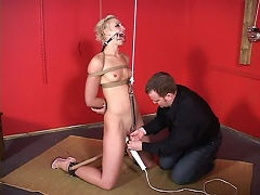 Short haired blonde bitch with small tits is  helplessly blindfolded, her hands are tied, and her mouth is gagged