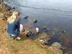 Cute blonde teen girl in mini jeans skirt Kitty Kim posing at the lake