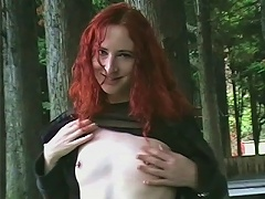 Redhead talkes off hger clothes in a public park where you can see people passing her by