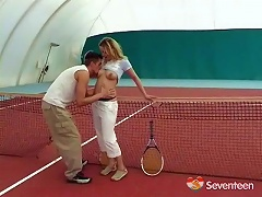 A young girl and a guy are at an indoor tennis court. The guy is touching the girl up and licking her ti