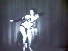 The famous stripper Kalantan is dancing on a stage, dressed in a black, exotic bikini and high heels. She sways her hi