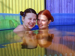 Two teenage girls are playing around in a small swimming pool outdoors. They lick at a couple of dildos and then conti