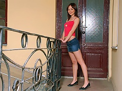 A young schoolgirl in shorts and T-shirt is standing on a verandah where she does a striptease, slowly ta