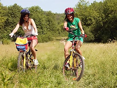 Two teenage girls are cycling through the fiels. When they arrive at a walled