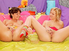 Two teenage girls are on the studio floor. They stroke each other gently, rubbing each others tits. After so