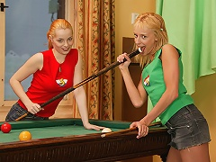 Two teenage girls are shooting pool and the chase each other around the pool table. They end up on top of it and d