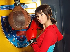 A young girl is posing in front of the camera wearing boxing gloves. She rubs herself all over, taking