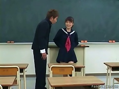 An Asian girl in a schoolgirls uniform is sitting in a classroom when a guy comes in. She seduces him, mas