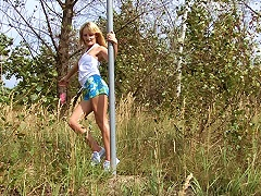 A blonde, long haired teenager is in the forest. She is doing a pole dance, using the pole of a tr